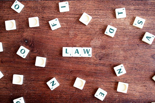 Law spelled out with scrabble tiles on a wooden table referring to the non-surgical facelift law.